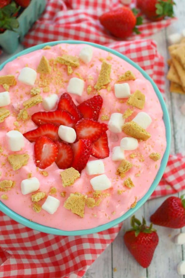 This creamy, delicious strawberry marshmallow fluff is the ultimate summer salad!  Made with fresh strawberries, marshmallows, cream cheese, Jell-o and whipped topping, this easy strawberry cheesecake fluff salad recipe will be your new go-to cookout dish!
