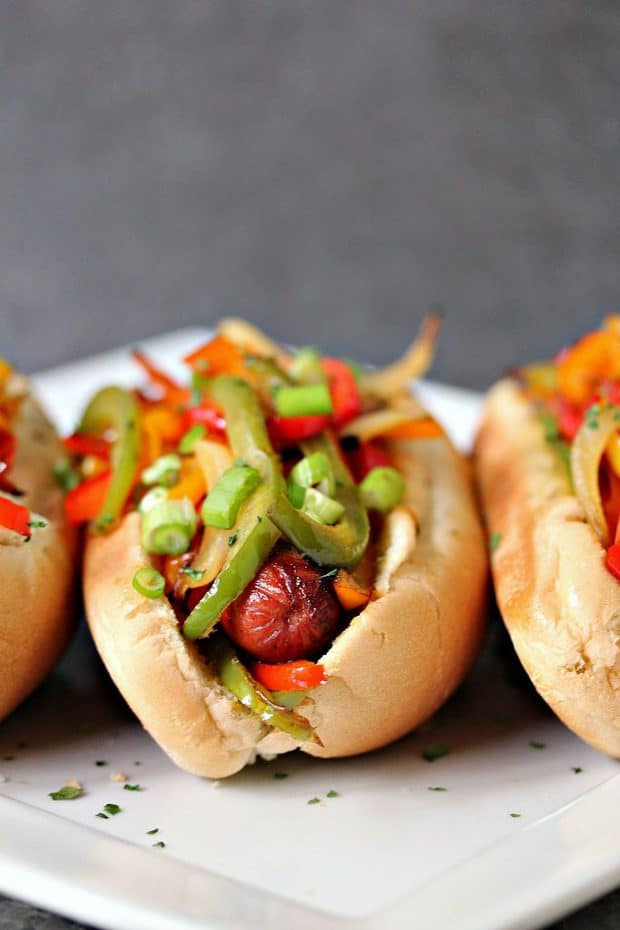 Grilled Hot Dogs topped with grilled bell peppers and onions. This recipe is incredibly easy to make, yet bursting with flavour. Be a legend at your grill this summer!