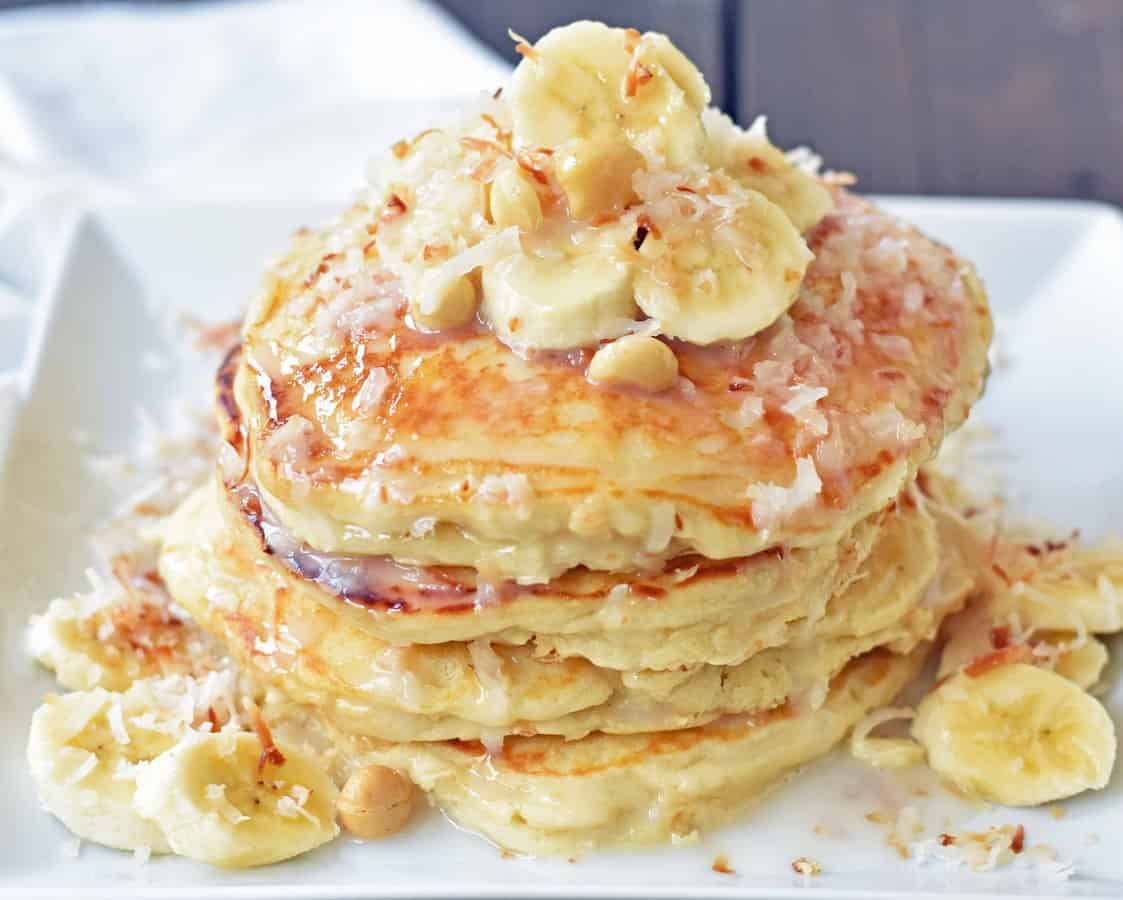Light and fluffy buttermilk pancakes studded with toasted coconut and topped with macadamia nuts, bananas, and a drizzle of homemade sweet coconut syrup. You will feel like you are sitting on a tropical island eating these pancakes!