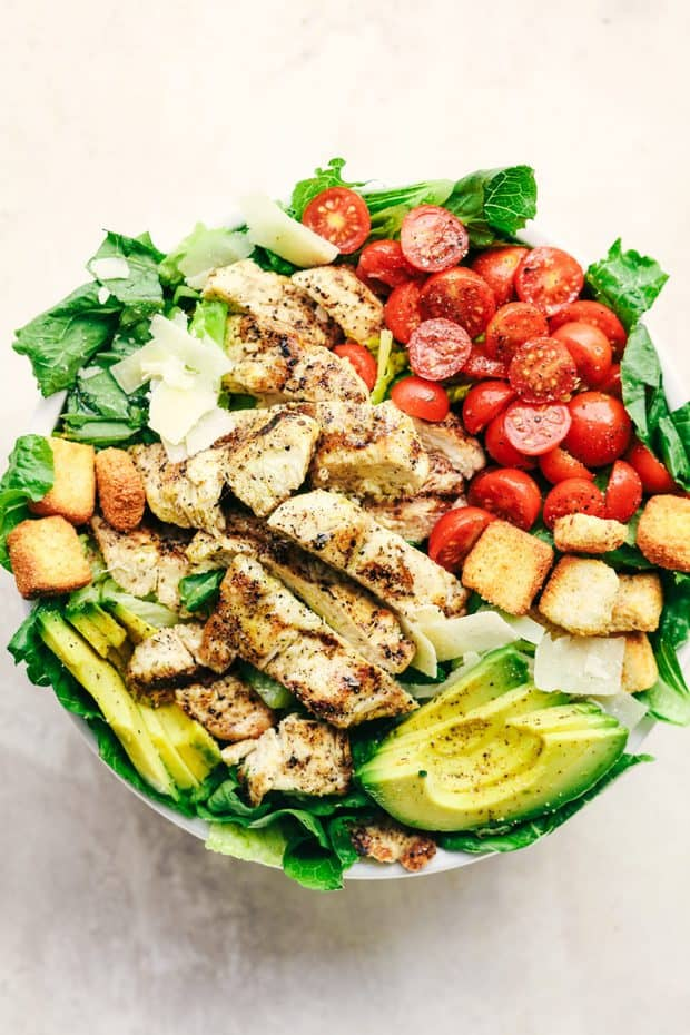 Grilled Chicken Caesar Avocado Salad is a mouthwatering classic salad with juicy grilled chicken, crisp romaine lettuce, cherry tomatoes, avocado, and topped with shaved mozzarella and crunchy croutons!