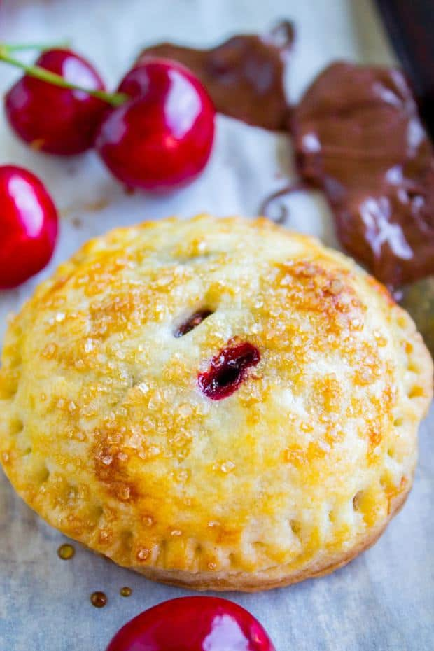 Flaky and buttery mini pies filled with fresh summer cherries and melty chocolate! The chocolate has a touch of almond in it. These are so perfectly cute it's hard not to throw down like 8 at a time.