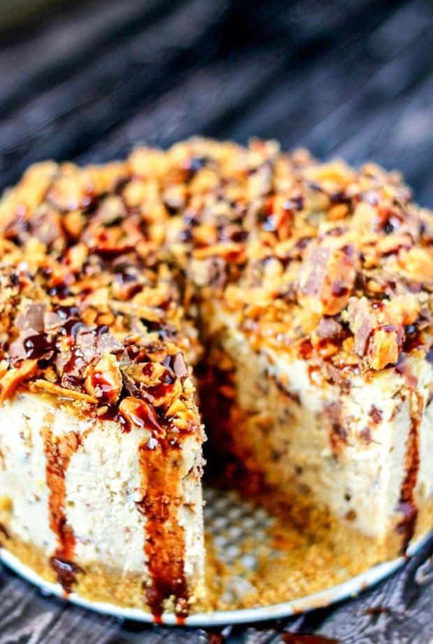 Slow Cooker Butterfinger Cheesecake is the creamiest, most delicious cheesecake you'll ever eat! With Butterfingers and chocolate sauce, it's amazing!