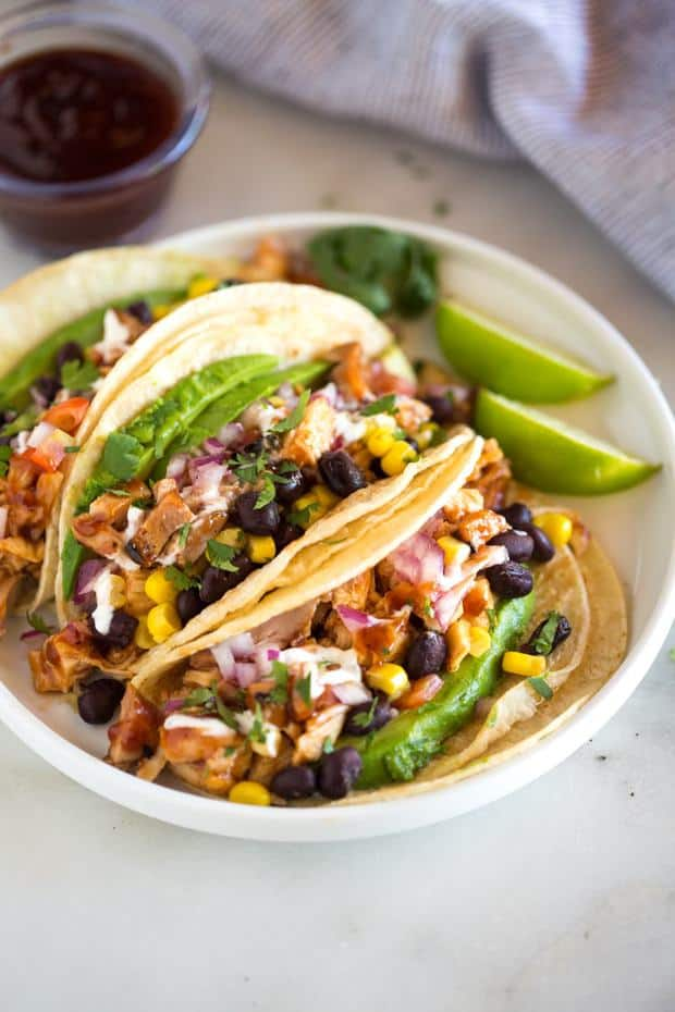 Grilled BBQ Chicken Tacos topped with black beans, corn, tomatoes and avocado with a creamy cilantro lime sauce. This easy and healthy meal will become a family favorite!