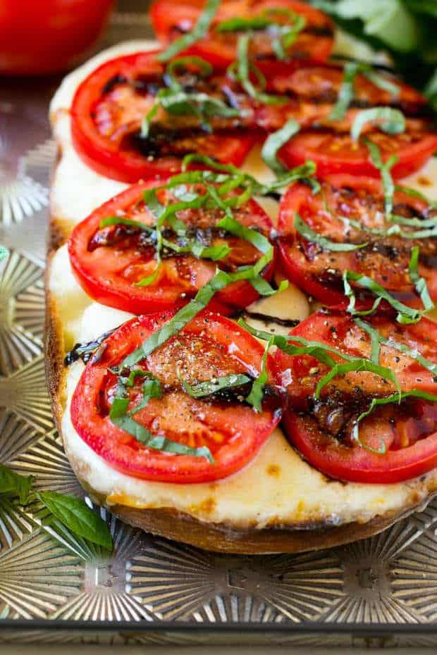 The recipe for Caprese Bread is a rustic loaf topped with melted mozzarella cheese, ripe tomatoes, basil and balsamic glaze.  The perfect summer dish!