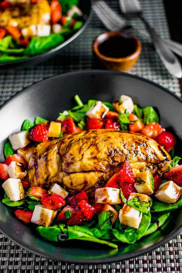 Liven up your salad routine with a strawberry caprese salad served with tender balsamic chicken, sweet fruit, and fresh mozzarella on a bed of baby spinach and drizzled with homemade balsamic glaze.
