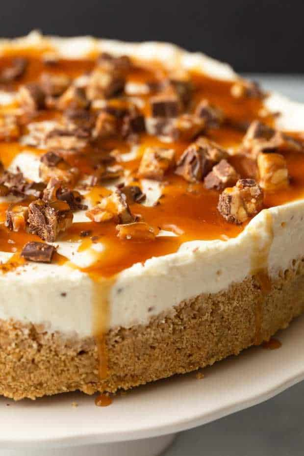 Decadent and silky No-Bake Snickers Cheesecake will satisfy all your dessert cravings. The creamy cheesecake filling is speckled with chopped Snickers candy bars and sits over a buttery graham cracker crust.