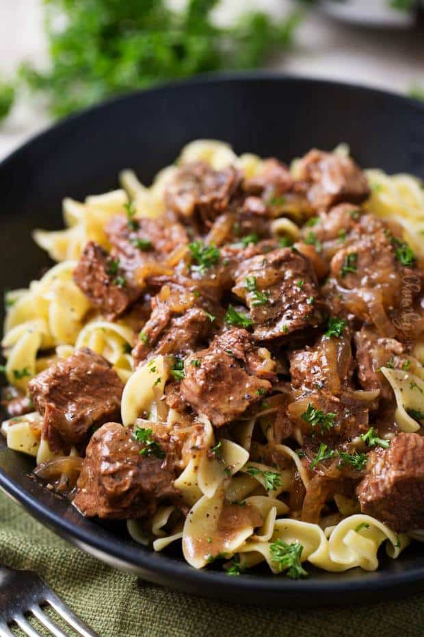 This slow cooker beef stew is made with Belgium beer and served over buttery egg noodles or mashed potatoes! The ultimate comfort food!